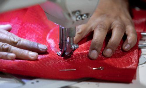 Man Sewing a Red Shade Sail